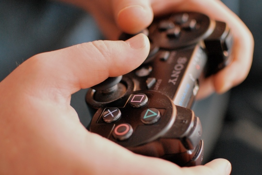 Hands holding Sony Playstation PS3 controller