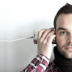 Man listening to tin can phone