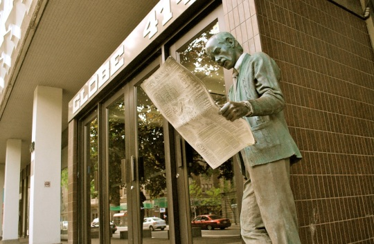 statue of man reading a newspaper